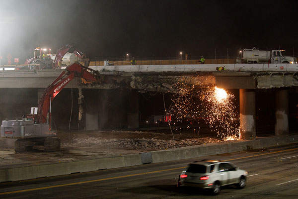 The east section of the Skirball Bridge is being demolished while traffic flows on the southbound lanes.