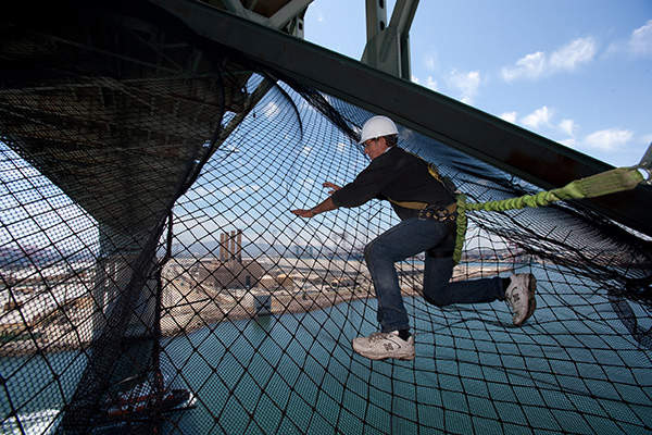 The existing Gerald Desmond Bridge is crumbling and is installed with netting to protect workers and ships from falling concrete chunks. Image courtesy of the Port of Long Beach.